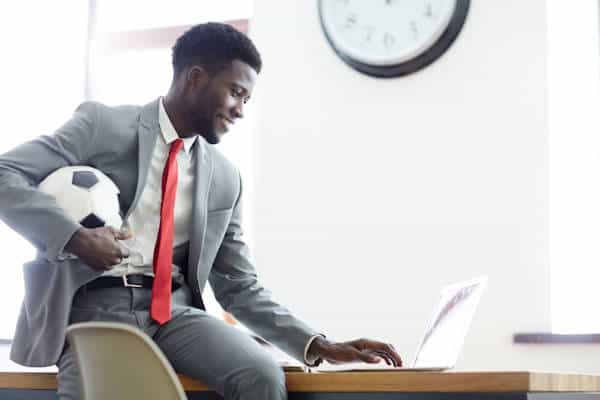 business man holding soccer ball in office
